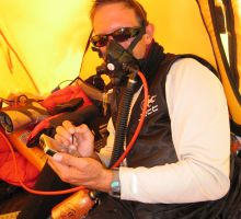 Paul writing a blog article while using oxygen from camp 3 on Everest