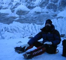 Paul putting crampons on to head up the mountain through the icefall