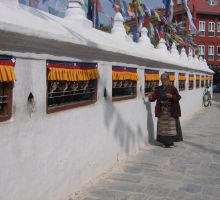 A nepalese woman spinning the prayer wheels in Kathmandu