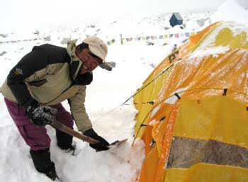 Dasona clearing snow from our tent. Photo Paul Adler
