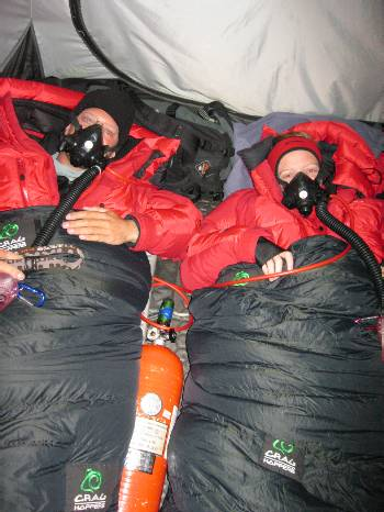 In our tent at C3 last night, wearing down suits inside our sleeping bags, and oxygen masks. The oxygen bottle is between us. Photo Paul Adler.