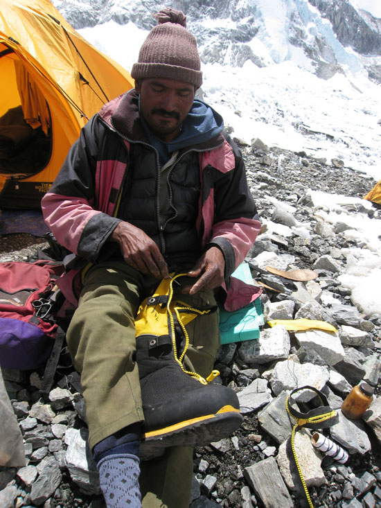 "The ""goo man"" fixes a broken La Sportiva Olympus Mons Evo climbing boot. The zipper had failed completely (you can see the broken one on the ground). We sewed two straps onto the boots as a temporary measure until we could get a replacement zipper and a skilled person to sew it on. Photo Paul Adler."