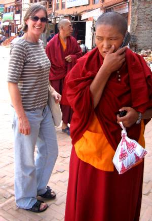 Liz stands behind this monk who was just taking a call on his mobile (cell) phone. Photo Fiona Adler